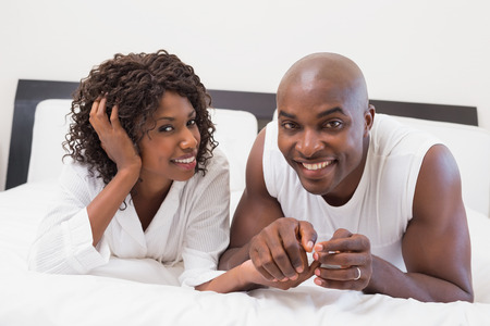 Happy couple lying on bed together at home in the bedroom photo
