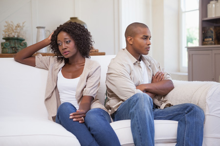 Unhappy couple not speaking to each other on sofa at home in the living room photo