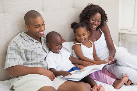 Happy family lying on bed reading book at home in the bedroom