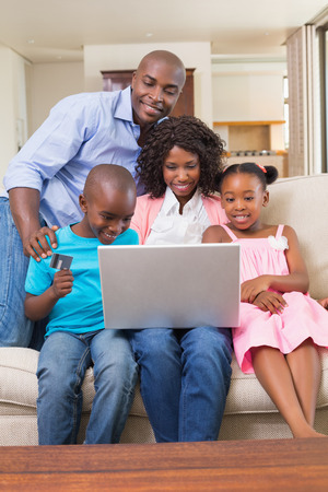 Happy family relaxing on the couch shopping online at home in the living room photo
