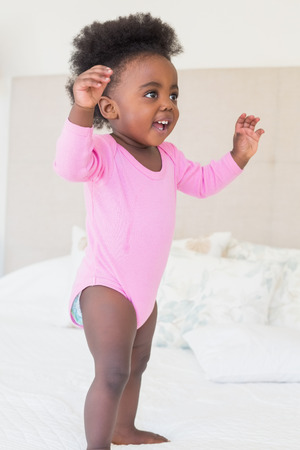 babygro: Baby girl in pink babygro standing on bed at home in the bedroom Stock Photo