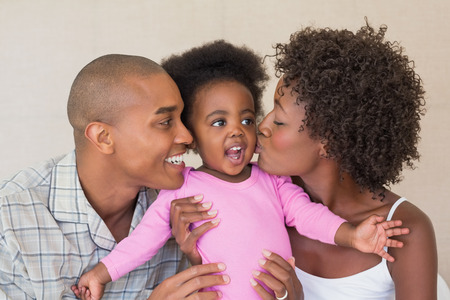 babygro: Happy parents and baby girl on bed together at home in the bedroom Stock Photo