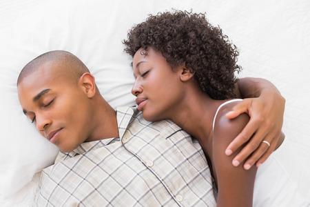 幸せなカップルの自宅寝室で一緒にベッドで寝ています。 写真素材