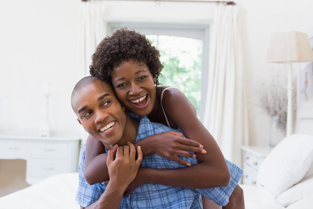 black couple: Happy couple messing about on their bed at home in the bedroom