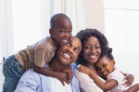 women black: Familia feliz posando juntos en el sof� en casa en la sala de estar