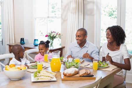 Famiglia felice godendo di un pasto sano insieme a casa in cucina