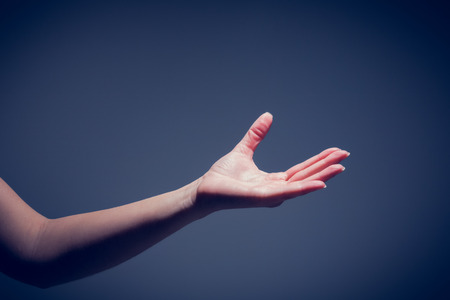 Female hand being held out on blue background Stock Photo