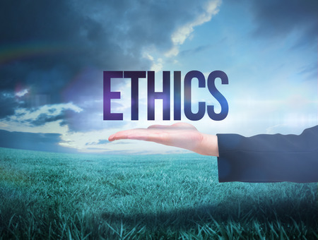 Businesswomans hand presenting the word ethics against blue sky over green field Standard-Bild