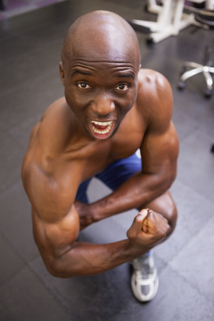 clenching: Portrait of a shirtless muscular man shouting while flexing muscles in gym