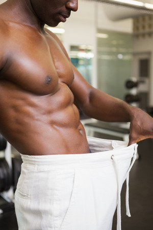 over sized: Mid section of a muscular man in an over sized pants at gym Stock Photo