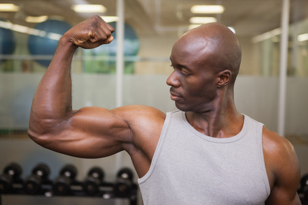 clenching: Portrait of a muscular man flexing muscles in gym