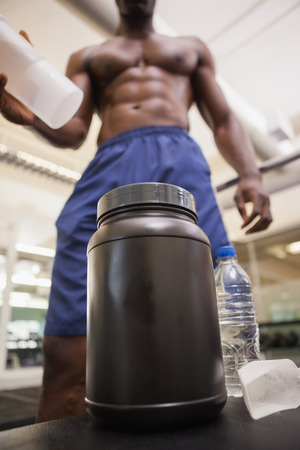 body builder: Shirtless body builder scooping up protein powder in gym Stock Photo