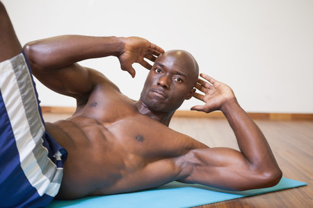 Portrait of a muscular man doing abdominal crunches in gym photo