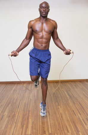 Portrait of a shirtless muscular man skipping in gym photo