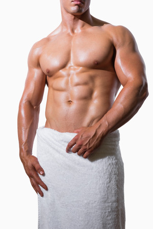 Mid section of a shirtless muscular man in white towel over white background Stock Photo