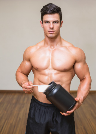Portrait of a shirtless body builder holding a scoop of protein mix in gym photo