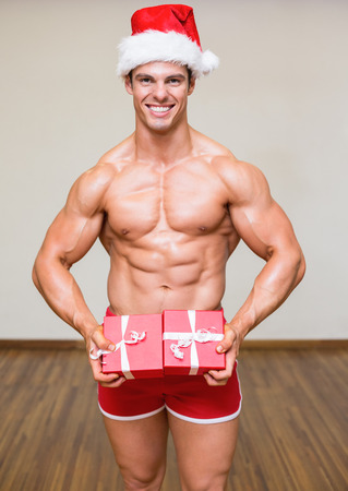 Portrait of shirtless macho man in santa hat holding gifts
