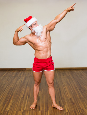 body builder: Full length of a male body builder in santa costume at the gym Stock Photo