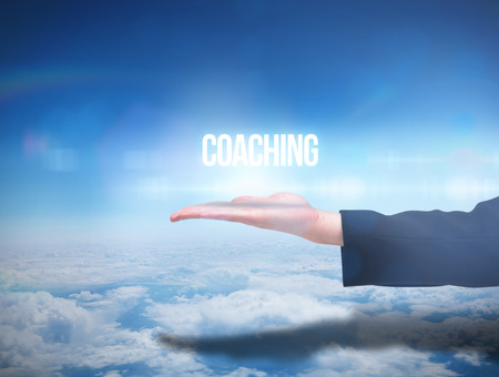 Businesswomans hand presenting the word coaching against blue sky over clouds at high altitude photo