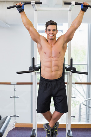 shirtless man: Shirtless male body builder doing pull ups at the gym