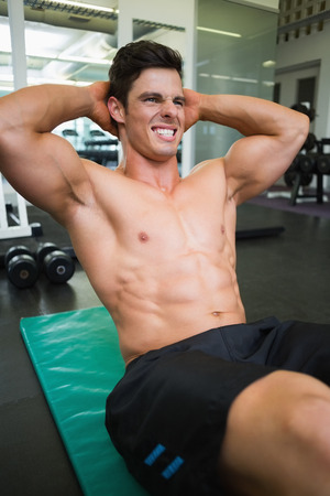 Determined young muscular man doing abdominal crunches in gym photo