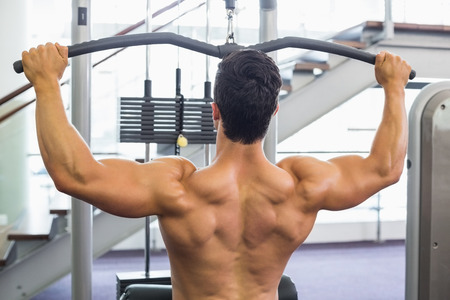 griping: Rear view of a muscular man exercising on a lat machine in gym Stock Photo