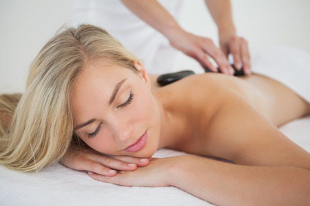 Beautiful blonde enjoying a hot stone massage at the health\ spa
