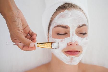 Beautiful blonde getting a facial treatment at the health spa Foto de archivo