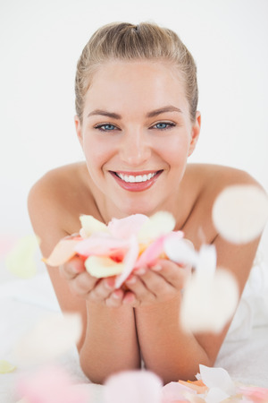 Pretty blonde lying on massage table holding petals at the health spa photo