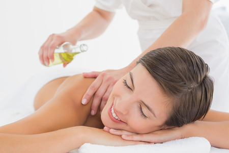 oil massage: Attractive young woman getting massage oil on her back at spa center