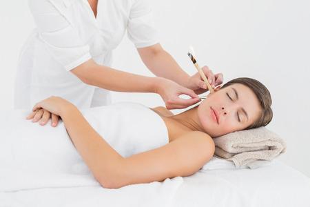 Seitenansicht einer schönen jungen Frau, die Ohrkerzenbehandlung im Wellnesscenter Standard-Bild
