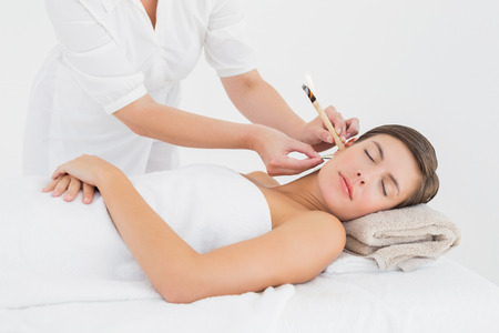 ear: Side view of a beautiful young woman receiving ear candle treatment at spa center Stock Photo