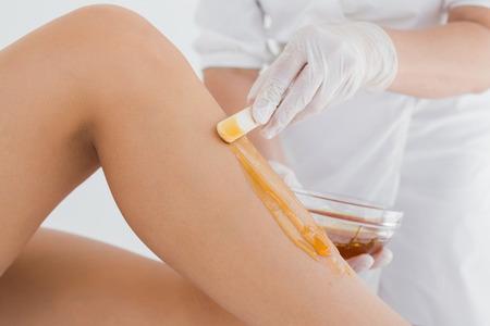 depilaciones: Mediados de secci�n de terapeuta depilaci�n pierna de la mujer en el centro de spa