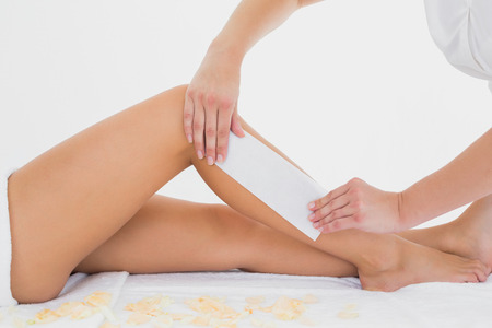 sexy legs: Mid section of therapist waxing womans leg at spa center