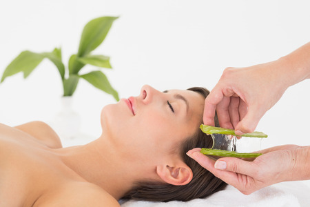 Side view of an attractive young woman receiving aloe vera massage at spa center photo