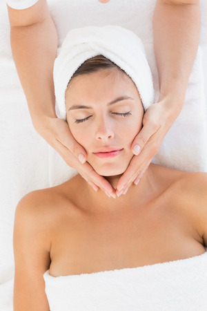 High angle view of an attractive young woman receiving facial massage at spa center photo
