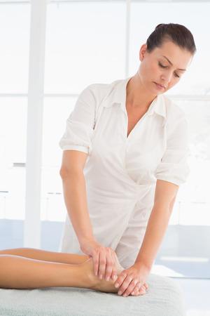 Female masseur massaging womans leg at spa center photo