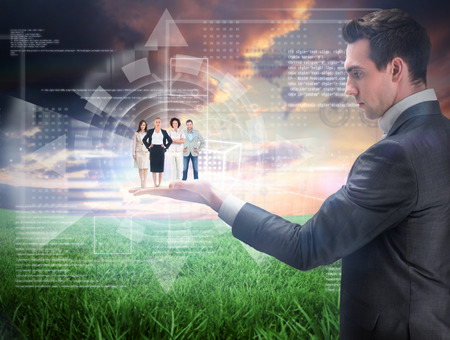 Business team looking at camera held by giant businessman against green field under orange sky photo