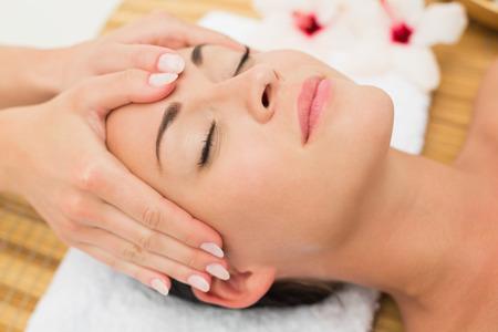 tratamiento facial: Brunette sonriente disfrutando de un masaje de cabeza en el balneario de la salud