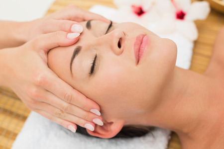 facial: Smiling brunette enjoying a head massage in the health spa