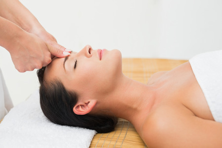 Smiling brunette enjoying a head massage in the health\ spa