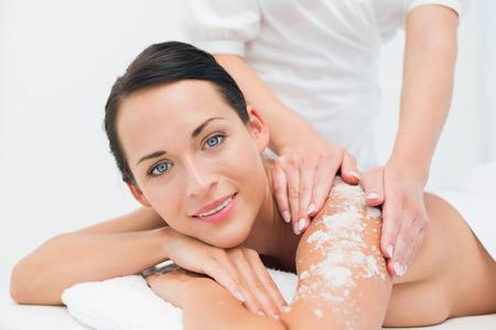 back massage: Peaceful brunette getting a salt scrub beauty treatment in the health spa Stock Photo