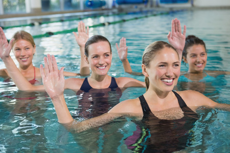 water aerobics: Smiling female fitness class doing aqua aerobics in swimming pool at the leisure centre