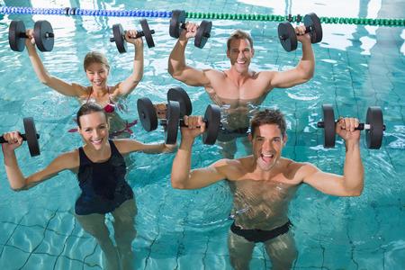 fitness hombres: Clase de fitness feliz haciendo aeróbic acuático con pesas de espuma en la piscina en el centro de ocio