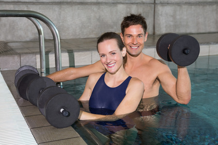 Happy couple working out with foam dumbbells in swimming pool at the leisure centre photo