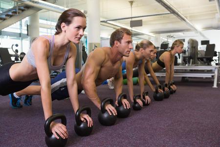actividad fisica: Clase de fitness en posici�n de tabla con pesas en el gimnasio