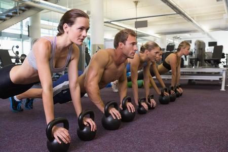 plank position: Fitness class in plank position with kettlebells at the gym Stock Photo