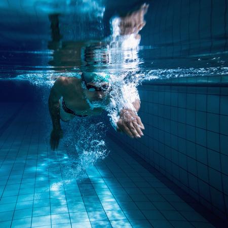 Fit zwemmer training door hemzelf in het zwembad van het recreatiecentrum Stockfoto