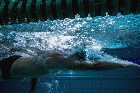 Fit swimmer training on his own in the swimming pool at the\ leisure centre