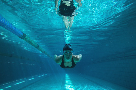 Athletic swimmer training on her own in the swimming pool at\ the leisure centre
